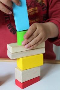 enfant empilant des formes en bois
